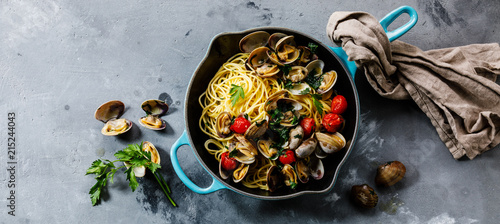 Pasta Spaghetti alle Vongole Seafood pasta with Clams in frying cooking pan on concrete background copy space