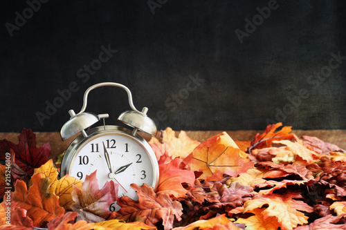 Fototapeta Alarm clock in colorful autumn leaves against a dark background with shallow depth of field. Daylight savings time concept. obraz