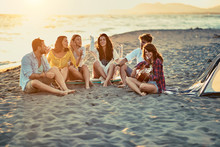 Friends With Guitar At Beach. Friends Relaxing On Sand At Beach With Guitar And Singing.