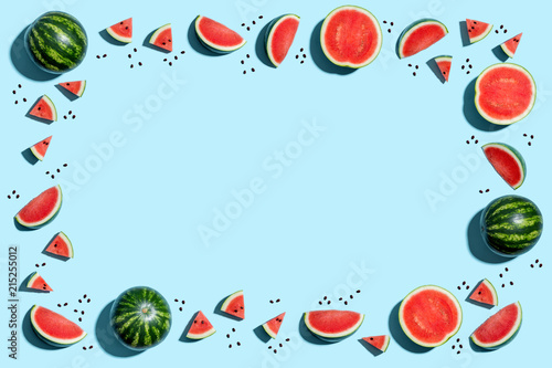 Whole and sliced watermelon border on a blue background