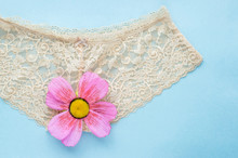 Beige Lace Briefs On A Blue Background. Concept Of Virginity