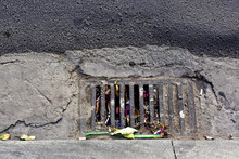 The Rain Grate On The Side Of The Road Is Full Of Rubbish