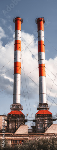 Staande foto Industrial geb. Vertical panoramic shot of the two colorful stack-furnaces with multiple metal supporting ropes, red and metallic colors, brick old factory building below, sunny summer day with cloudy sky