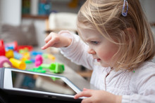 Female Toddler Playing On A Tablet