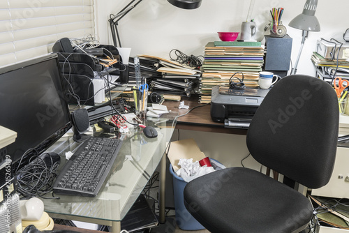 Messy office with clutter filed desk, piles of file folders and notebooks.