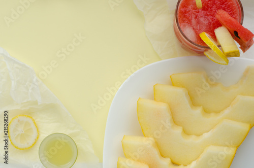 Staande foto Zuivelproducten Glass of red watermelon smoothie with ice and limoncello and slices of melon and watermelon on white plate