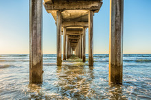 Symmetrical Shot Under Scripps Pier With Poles, Pillars, Sunny Sunlight, Sun, Blue Sky, Waves During Golden Sunset In La Jolla, San Diego, California