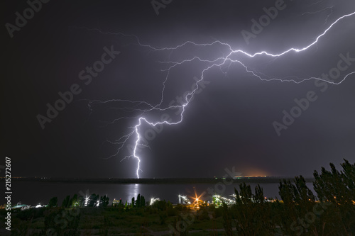 Bright flash of night lightning on the river bank. Poster