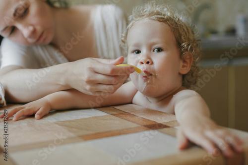 Poster Artist KB Mother feeds a little girl