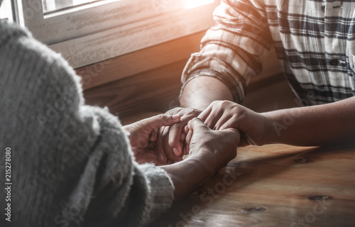 Fotografija Two christianity sitting around wooden table and holding hands with praying to God together
