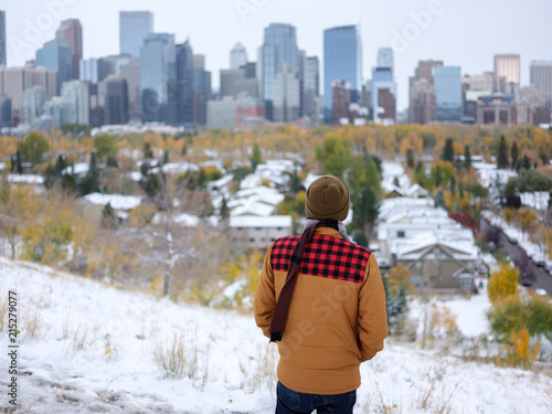 A man looks at the skyline of a city on a snowy autumn day