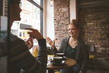 Couple Talking Over The Coffee At Cafe