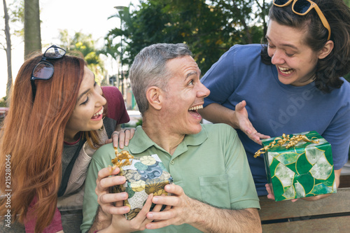 Fotografia, Obraz  Teen son and daughter surprise dad by giving a present