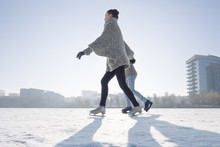 Young Couple Ice Skating On The Lake