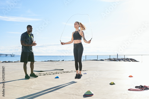 Instructor training young woman on sports ground