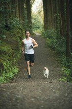 Man Jogging With His Dog In Lush Forest