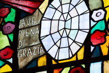 Pavia, Italy. 2018/2/13. Stained Glass In A Church With The Words: 'Ave Piena Di Grazia' Meaning 'Hail [Mary], Full Of Grace' In Italian. Santa Maria Del Carmine (the Church Of Holy Mary Of Carmel).