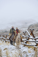 Cowboy And Cowgirl Riding On Horses Beside Fence In Snow, Rocky Mountains, Wyoming, USA