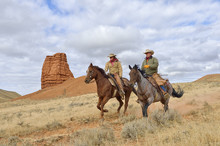 Cowboy And Cowgirl Riding Horses With Castel Rock In The Background, Shell, Wyoming, USA