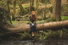 Woman Sitting On Fallen Tree Trunk Near River