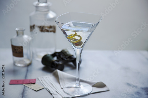 Tuinposter Alcohol Martini in glass on napkin with opera glasses, tickets and vintage bottles