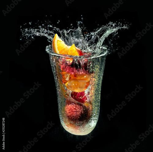 Refreshing fruit dessert in imaginary glass out of water splash on black background Fototapete