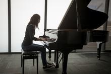 Schoolgirl Playing Piano In Music School