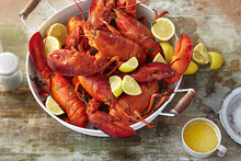 Pot Full Of Cooked Whole Lobster With Sliced Lemon And Melted Butter On Wooden Tabletop