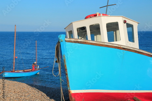 Colorful fishing boat on a pebble beach in village of Beer in East Devon