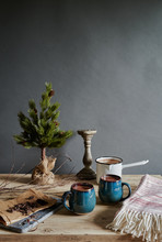 Hot Chocolate: Hot Chocolate Drinks In Green Mugs On Wooden Table With Small Coniferous Tree In Background.