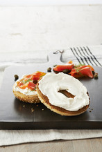 Toasted Sesame Seed Bagel Topped With Cream Cheese, Smoked Salmon, Dill And Capers On Wooden Cutting Board, Studio Shot