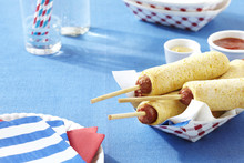 Homemade Corn Dogs In A Paper Serving Container With Paper Plates, Napkins, Glasses And Straws, Studio Shot On Blue Background