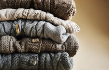 Close-up Of Stack Of Five Cardigans, Studio Shot On Brown Background