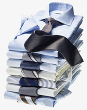 Stack Of Multi Coloured Shirts With Ties On White Background