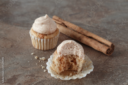 Delicious Fresh Baked Cinnamon Mini Cupcakes With Frosting and Cinnamon Stick pl Poster