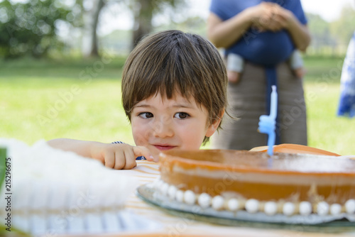 Three year old boy looking at a cake on a table outdoors in summer