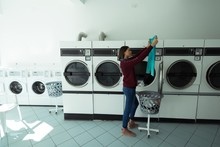 Woman Checking Her Clothes At Laundromat