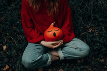 Woman Holding A Halloween Pumpkin With A Surprised Face Painted