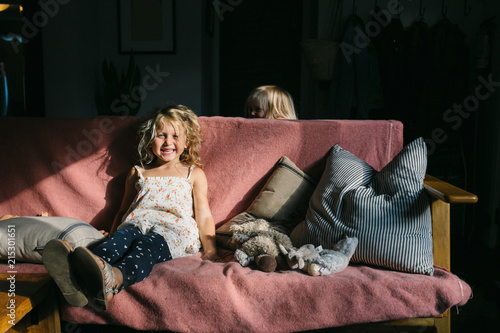 Cute little girls on couch in sunlight