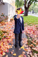 Boy In School Uniform Holding Out An Autumnal Leaf