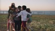 portrait of happy group of children group hug enjoying fun games on seaside beach park at sunset