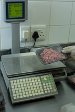 Butcher Checking Weight Of Packed Meat