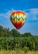 Red, Yellow, Orange, Green, and White Teardrop Shaped Hot Air Balloon Over Corn Field on Sunny Day with Trees and Cloudy Blue Sky in Background