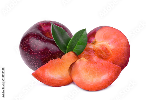 whole and slices red plum with green leaves isolated on white background
