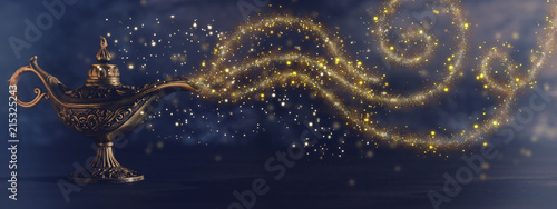 Stampa su Tela  Image of magical mysterious aladdin lamp with glitter sparkle smoke over black background