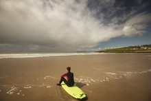 Surfer Sitting On The Surfboard On Beach And Looking At Sea