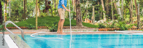 Fototapeta Cleaner of the swimming pool . Man in a blue shirt with cleaning equipment for swimming pools, sunny BANNER, long format obraz