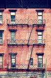 Old red brick building with fire escapes, one of the New York City symbols, color toned picture, USA.  - 215337430