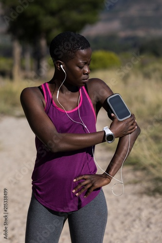 Female athlete listening to music from smartphone mp3 player