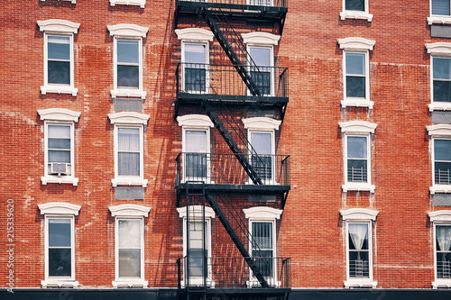 Poster New York City Old red brick building with fire escapes, one of the New York City symbols, color toned picture, USA.